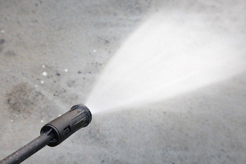 Water hose spray gun washing his cement floor